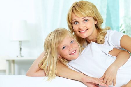 Portrait of a loving mother and her cute little daughter looking at camera with a smile Stock Photo - 12381106