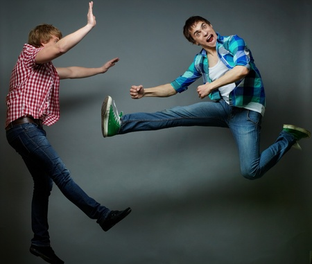 Guy jumping into air and kicking his friend, fool�s day series photo