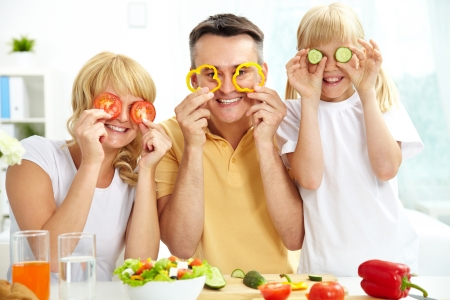 Cheerful family playing with vegetables in kitchen, healthy food photo