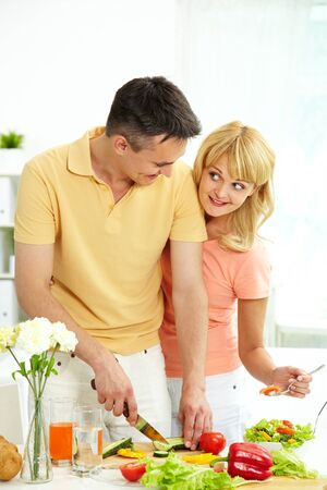 Vertical shot of loving couple cooking healthy food together photo