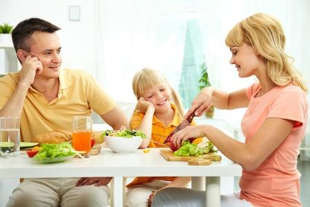 niños desayunando: Familia de tres a la mesa de comer verduras frescas