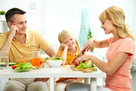 Family of three at table eating fresh vegetables photo