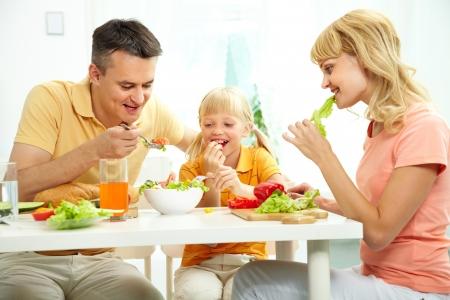 familia comiendo: Familia de tres, junto a la mesa comiendo ensalada fresca