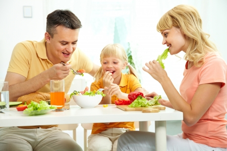 family eating: Familia de tres, junto a la mesa comiendo ensalada fresca