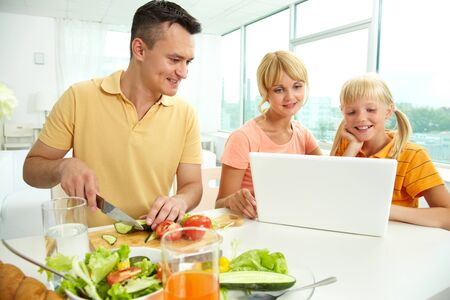 Mother and daughter using laptop while father cutting fresh vegetables photo