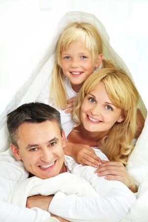 Playful family hiding under blanket isolated on white background photo