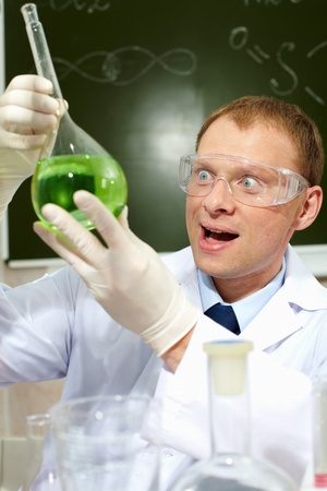 obtained: Happy male scientist looking at a new substance obtained in laboratory