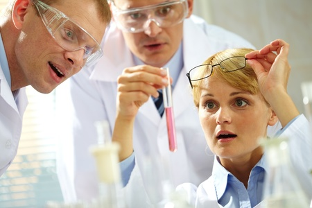 Three inspired scientists looking at a substance discovered in a lab photo