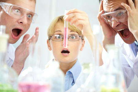 startled: Three shocked scientists looking at the obtained substance expressing intense emotions Stock Photo