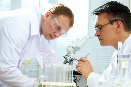 specimen: Scientist looking at specimen while his assistant helping him