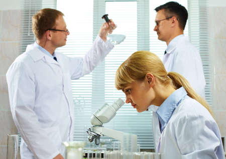 Team of scientists analyzing different substances at the laboratory photo