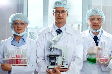 Three serious scientists holding lab equipment and looking at camera photo