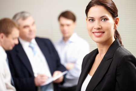 Portrait of a confident businesswoman smiling and looking at camera while his colleagues discussing a project Stock Photo - 12381097