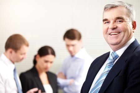 subordinates: Portrait of a cheerful mature businessman smiling and looking at camera