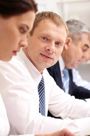 Handsome man taking part in business meeting and smiling at camera Stock Photo - 12381127