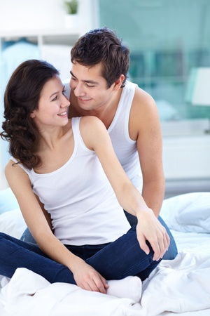 Young people sitting in bed together looking affectionately at each other Stock Photo - 12381131