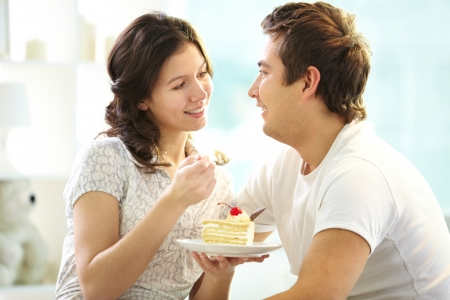 Loving couple eating cake together photo