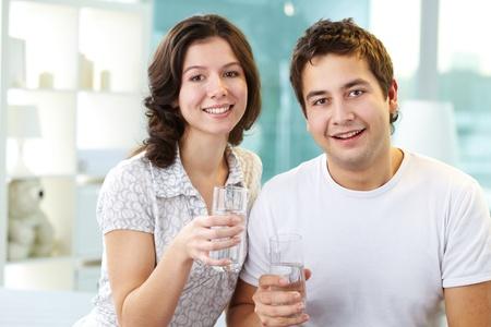 hombre sentado: Los j�venes enamorados celebraci�n de vasos de agua y mirando a c�mara Foto de archivo