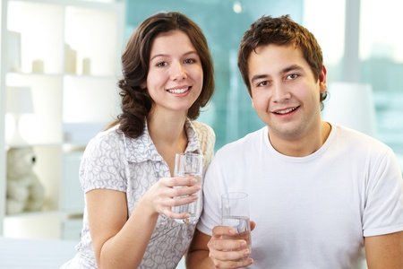 casal: Young lovers holding glasses of water and looking at camera