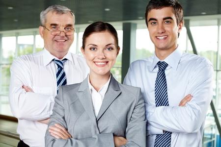 Drie lachende mensen uit het bedrijfsleven kijkt vol vertrouwen naar de camera Stockfoto