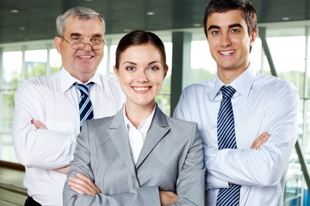 Three smiling business people looking confidently at camera photo