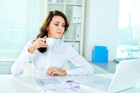 Beautiful business woman looking at laptop screen and drinking tea coffee photo