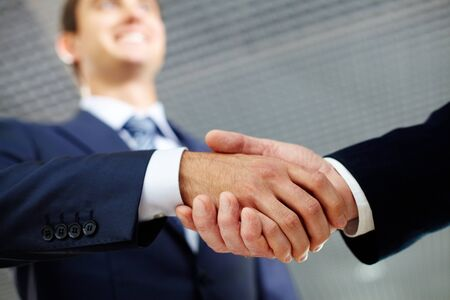 Two businessman shaking hands greeting each other photo