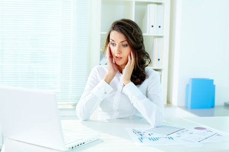 worried executive: Shocked business lady looking at the screen of laptop Stock Photo