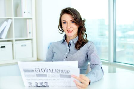 Portrait of a confident business lady reading a fresh newspaper photo