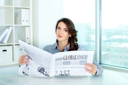 Young business woman holding a newspaper and looking at camera photo