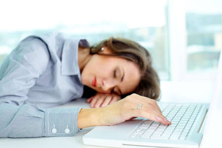 Young woman sleeping at workplace, her fingers touching keyboard photo