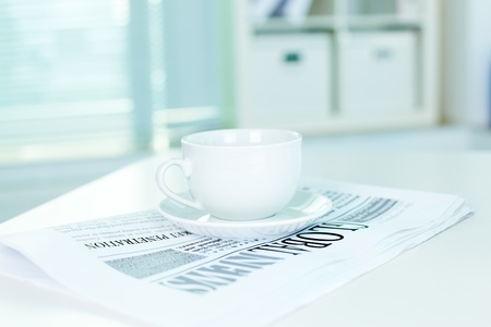 A still of white cup standing on a fresh newspaper in office photo