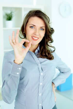 Young woman making an OK gesture and looking at camera Stock Photo - 12381128