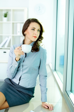 Beautiful woman drinking coffee and looking dreamingly in the office window photo