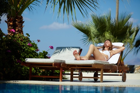 Young woman in bikini lying on chaise lounge in the sunlight Stock Photo - 12620714