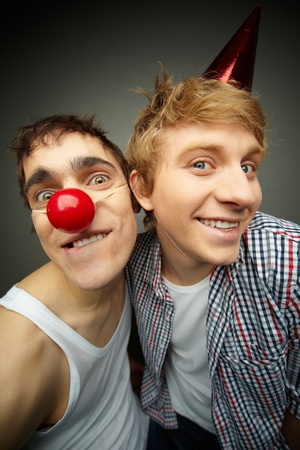 Two funny guys looking at camera and smiling crazily, fool�s day series photo