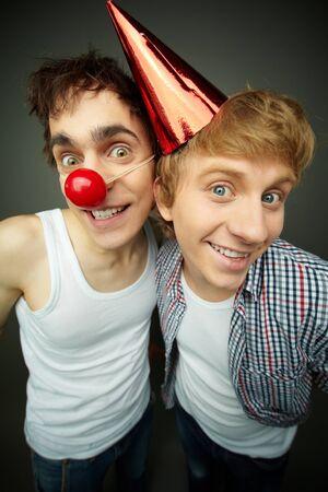 tonto: Dos chicos divertidos mirando a la cámara y sonriendo como locos, tontos serie de días