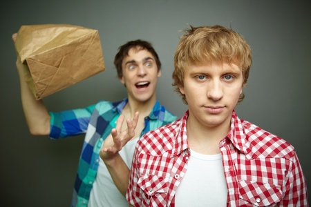 Crazily looking guy exploding paper bag behind his friend's back, fool's day series photo
