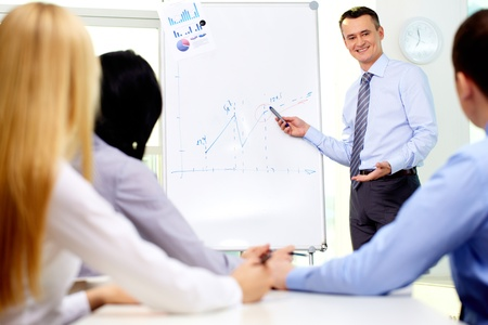 Smiling businessman drawing a graph for his colleagues on the whiteboard Stock Photo - 12620704