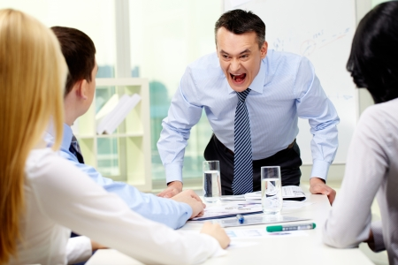 bawl: Angry businessman shouting at his workers with an expressive look Stock Photo