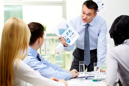 employment issues: Business worker showing charts and graphs to his employees with a furious look
