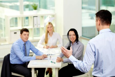 Businessman presenting new product or device to his smiling colleagues photo