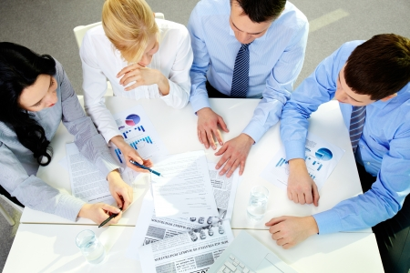project planning: The above view of a business team working with documents