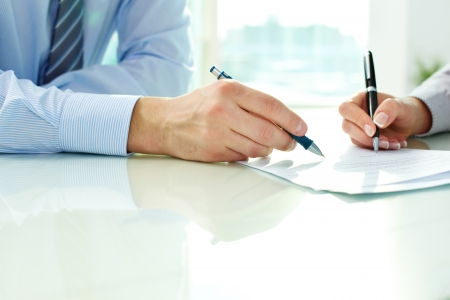 Two business partners signing a document (signing, contract,\ agreement)