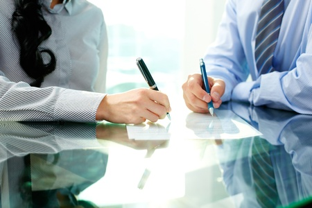 holding a sign: Two business people signing a document Stock Photo