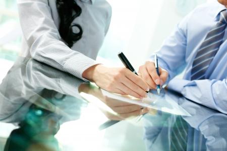 firmando: Incline hacia arriba de los dos socios de trabajo, la firma de un contrato y cerrar el trato