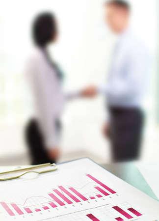 cuadro sinoptico: Primer plano de gr�ficos de negocios con figuras borrosas de los trabajadores de oficina en el fondo