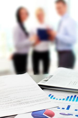 Close up of business graphs with blurred figures of office workers in the background Stock Photo - 12620770