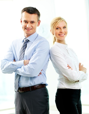 subordinates: Two business people standing back to back and smiling at camera