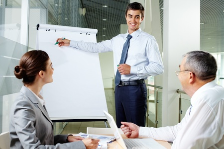 Handsome manager presenting business project to his team Stock Photo - 12620776